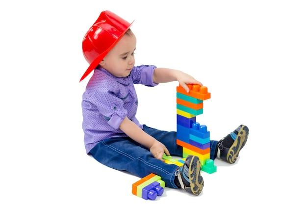 Criança brinca de construtor com o construtor sentado no chão
