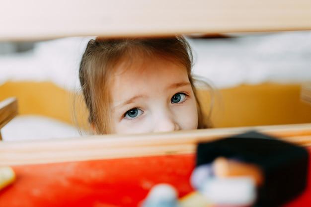 Criança brinca de esconde-esconde. a criança se escondeu atrás da prancheta no berçário. visível apenas rosto feliz