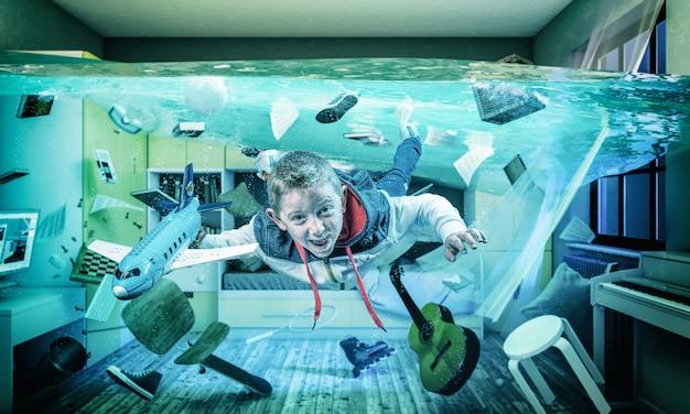 Criança brinca feliz com um avião em sua sala inundada.