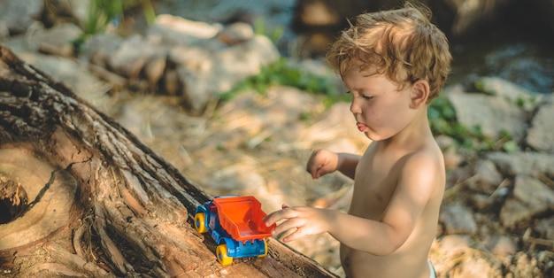 Criança brincando ao ar livre. criança, despejamos a areia no caminhão vermelho. jogos infantis de rua. um menino brincando com uma máquina no grande tronco