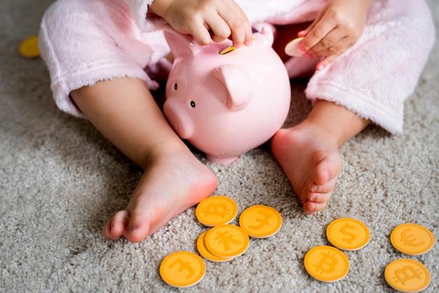 Criança brincando colocando moedas em piggybank
