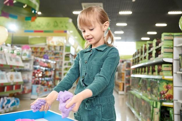 Criança brincando com areia cinética na sala de jogo da loja.