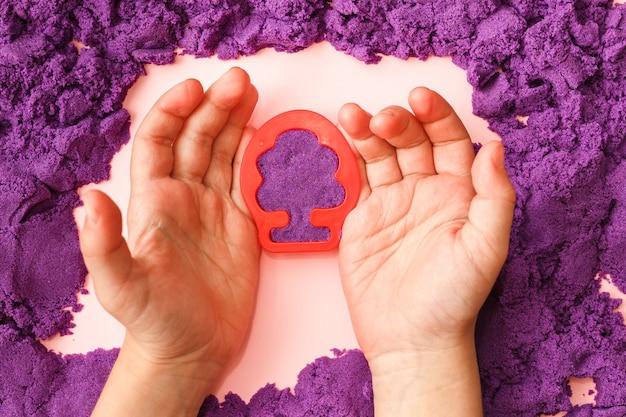 Criança brincando com areia cinética violeta e bolor de árvore