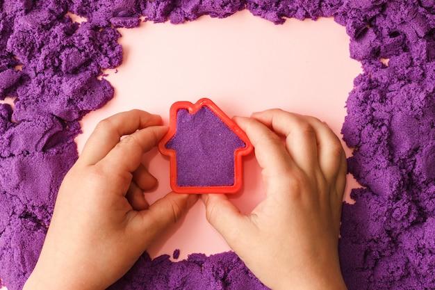 Criança brincando com areia cinética violeta e bolor de casa