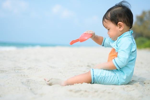 Criança brincando com areia na praia à beira-mar. férias com crianças perto do mar.