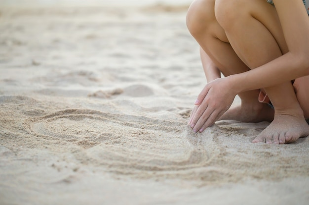 Criança brincando com areia na praia, menina brincando ao ar livre, pôr do sol à noite
