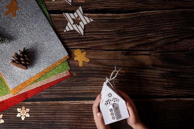 Criança brincando com artesanato de natal em fundo de madeira. artigos de férias em uma mesa.