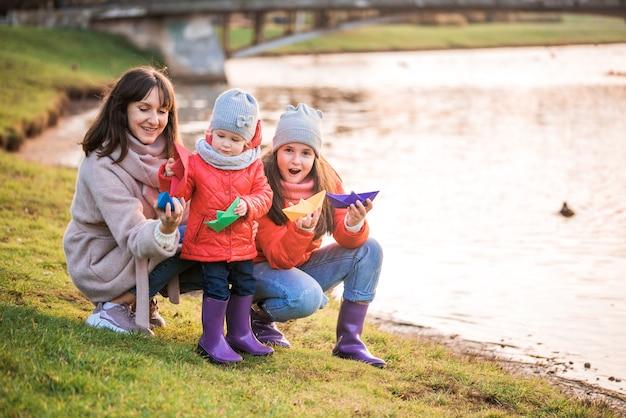Criança brincando com barquinhos de papel na primavera water.lake ou rio.