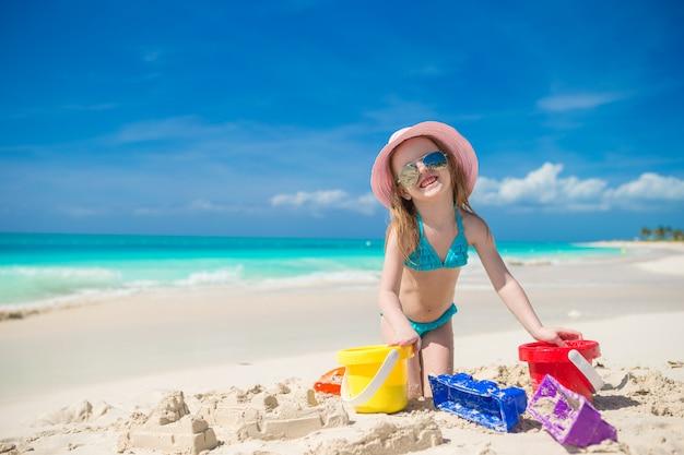 Criança brincando com brinquedos de praia durante as férias tropicais