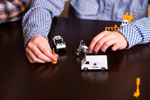Criança brincando com carros de brinquedo.