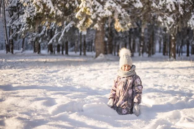 Criança brincando com neve no inverno. crianças pegam flocos de neve