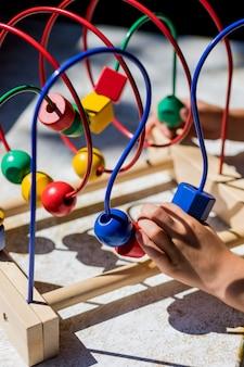 Criança brincando com o brinquedo bead maze no jardim mais gentil. o labirinto de contas de madeira. crianças aprendendo cores, forma e count.fine habilidades motoras.