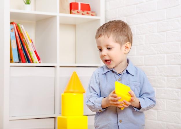 Criança brincando com o construtor no chão em casa. crianças em idade pré-escolar se divertindo. creche, desenvolvimento infantil. tijolos de plástico coloridos no chão.