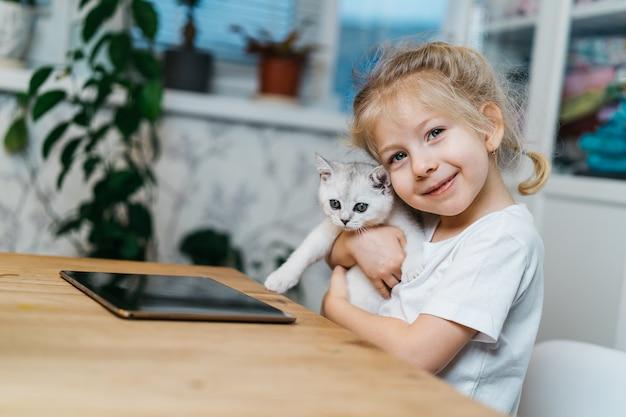 Criança brincando com o gatinho. uma menina segura um gatinho branco. uma menina se aconchega a um animal de estimação fofo e sorri enquanto está sentada na sala de estar da casa. crianças e animais de estimação felizes.