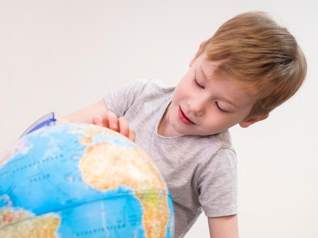 Criança brincando com o globo da terra