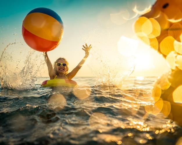 Criança brincando com pato de borracha e bola no mar.
