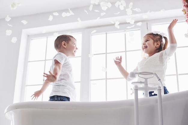 Criança brincando com pétalas de rosa no banheiro em casa. menina e menino fawing diversão e alegria juntos. o conceito de infância e a realização de sonhos, fantasia, imaginação