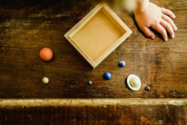 Criança brincando com planetas de brinquedo pequeno em uma velha mesa de madeira.