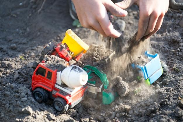 Criança brincando com tratores de brinquedo de plástico no quintal