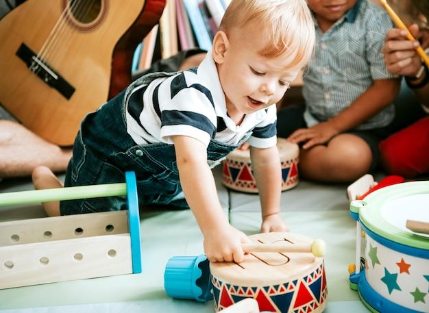 Criança brincando com um conjunto de tambores de madeira