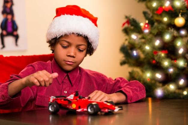 Criança brincando com um presente de natal.