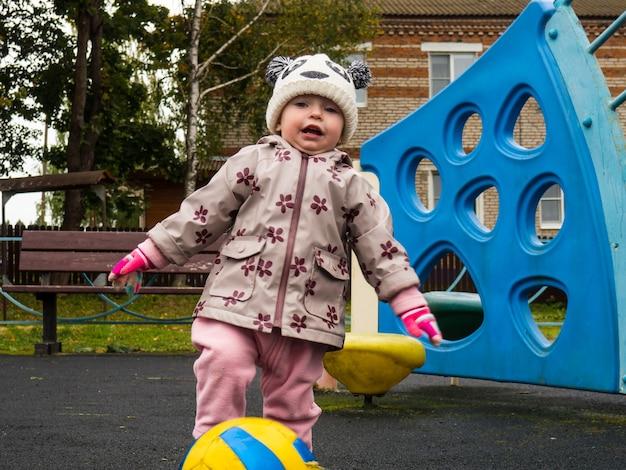 Criança brincando com uma bola no parquinho em um dia de outono