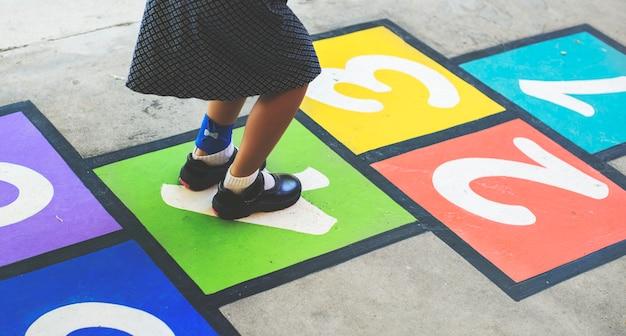 Criança brincando de amarelinha na escola