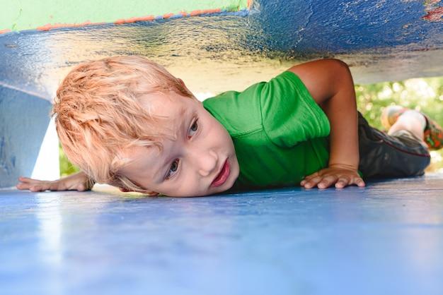 Criança brincando de esconde-esconde em um labirinto de concreto urbano à procura de diversão para seus amigos.