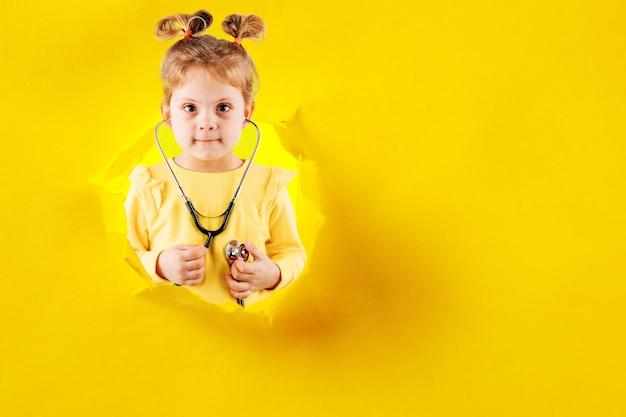 Criança brincando de médico com estetoscópio nas mãos. garota garoto sorridente feliz jogando em casa