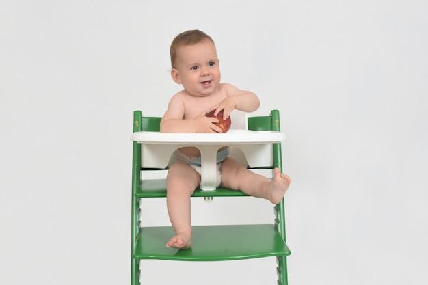Criança brincando de pêssego em uma cadeira alta no fundo branco