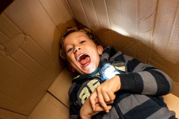 Criança brincando dentro de uma caixa de papelão.