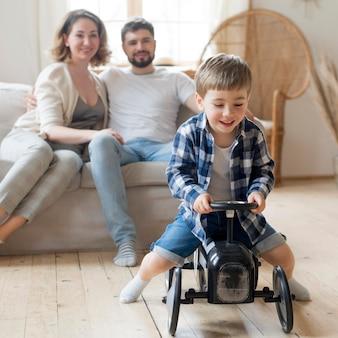 Criança brincando e pais sentados no sofá