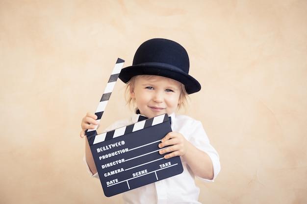 Criança brincando em casa. criança segurando claquete. conceito de cinema retro