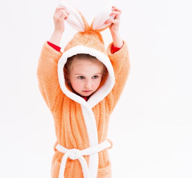 Criança brincando em roupão com orelhas de coelho