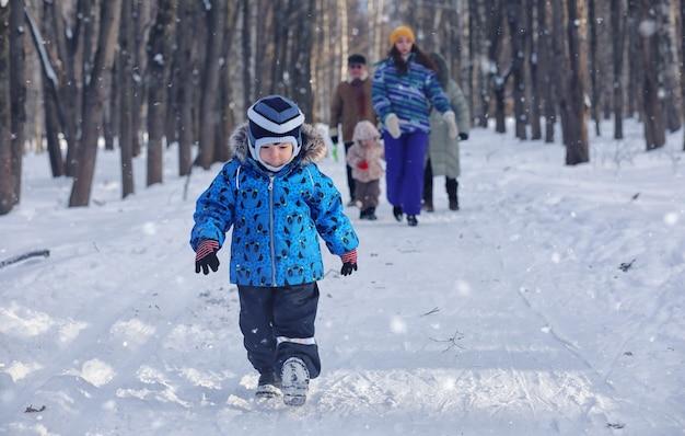 Criança brincando em um parque de inverno e se divertindo com a família