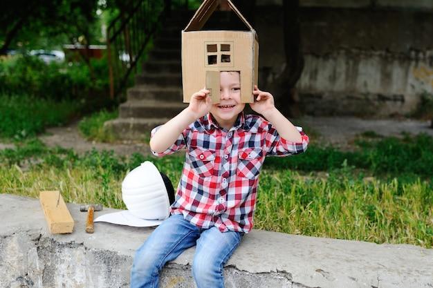 Criança brincando em uma casa de brinquedo de papelão