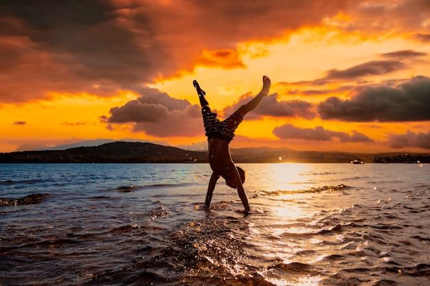Criança brincando no mar ao pôr do sol.
