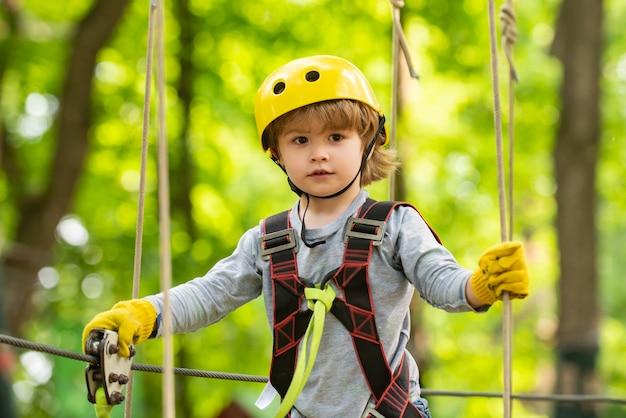 Criança brincando no parquinho. criança feliz subindo em um playground de corda ao ar livre. aventura