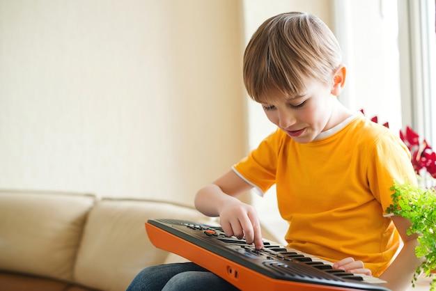 Criança brincando no sintetizador em casa. piano infantil.