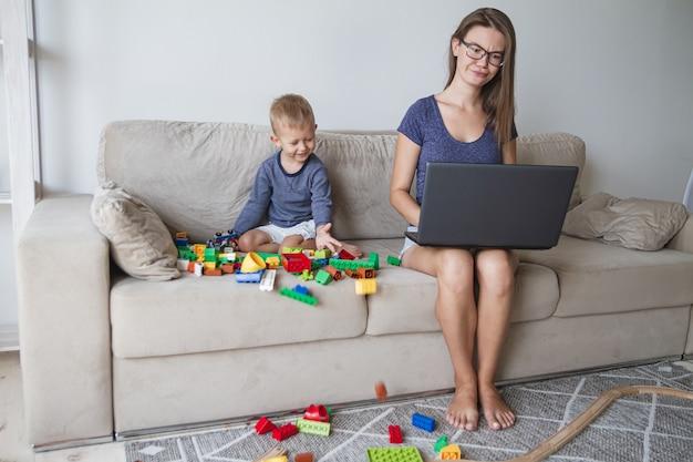 Criança brincando no sofá enquanto a mãe trabalha no laptop