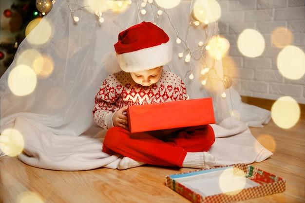 Criança brincando perto da árvore de natal com presentes na véspera de natal