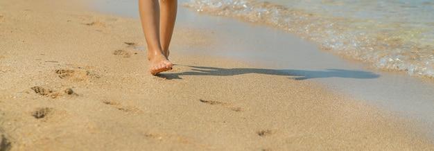 Criança caminha ao longo da praia deixando pegadas na areia.