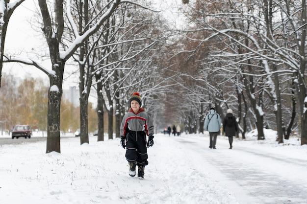 Criança caminha no parque coberto de neve de inverno. garotinho em uma caminhada.