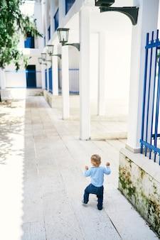 Criança caminha sobre ladrilhos de pedra no pátio de uma casa grande com cerca de treliça