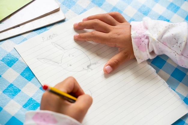 Criança canhota irreconhecível, desenhando um coelho de desenho animado em um pedaço de papel. menina, segurando um lápis e explorar a criatividade. lazer para o conceito de crianças. estilo de vida com crianças em casa.