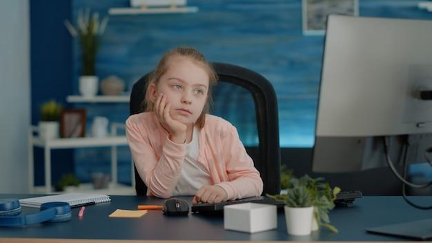 Criança cansada assistindo aula online no computador