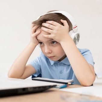 Criança cansada de tiro médio com fones de ouvido