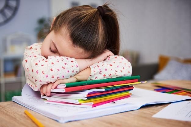 Criança cansada e entediada dormindo sobre livros
