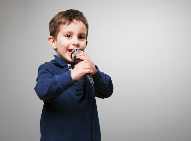 Criança cantando através de um microfone