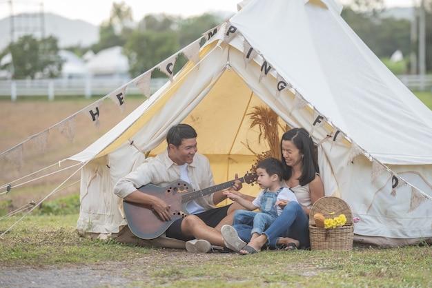 Criança cantando com a família sorridente no acampamento. família aproveitando o acampamento de férias na zona rural.